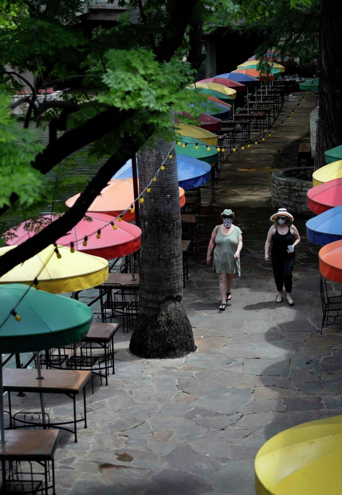 Visitors walk past a restaurant on the River Walk that is preparing to open soon, Tuesday, May 12, 2020, in San Antonio. The restaurant has been closed due to the COVID-19 pandemic and will open with limited seating and make use of social distancing practices. (AP Photo/Eric Gay)