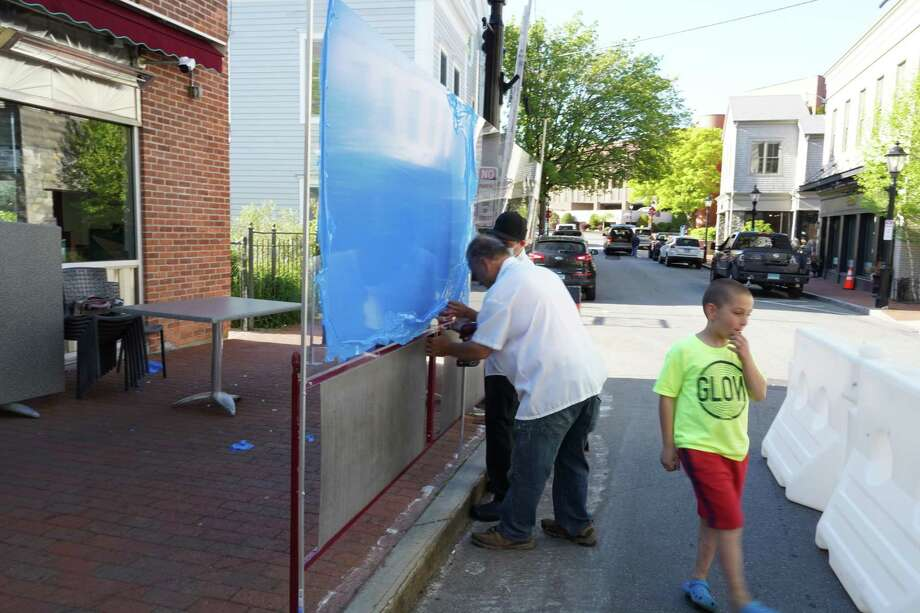 Belmar Cante and owner of New Canaan Diner Teddy Giapoutzis work at hanging a plexiglass divider between patrons and the walk area on Forest Street in New Canaan on Thursday, May 21. This is an example of restaurants using ingenuity to help patrons stay safe while dining out during the coronavirus pandemic. Photo: Grace Duffield / Hearst Connecticut Media