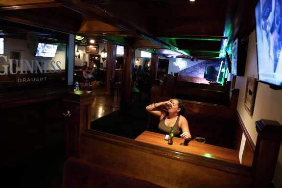Jessica Ford takes a shot of Jose Cuervo tequila at The Winchester pub a few moments after the establishment opened its doors for the first legal drinks in a San Antonio bar in nearly two months at 12:01 am on Friday.