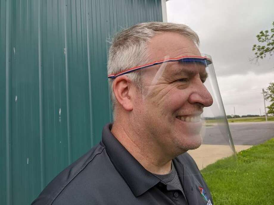 Tom Whitten, manager of the Lewis and Clark Community College's St. Louis Confluence Fab Lab in Edwardsville, demonstrates a face shield using a plastic headband created by 3D printers at the lab.
