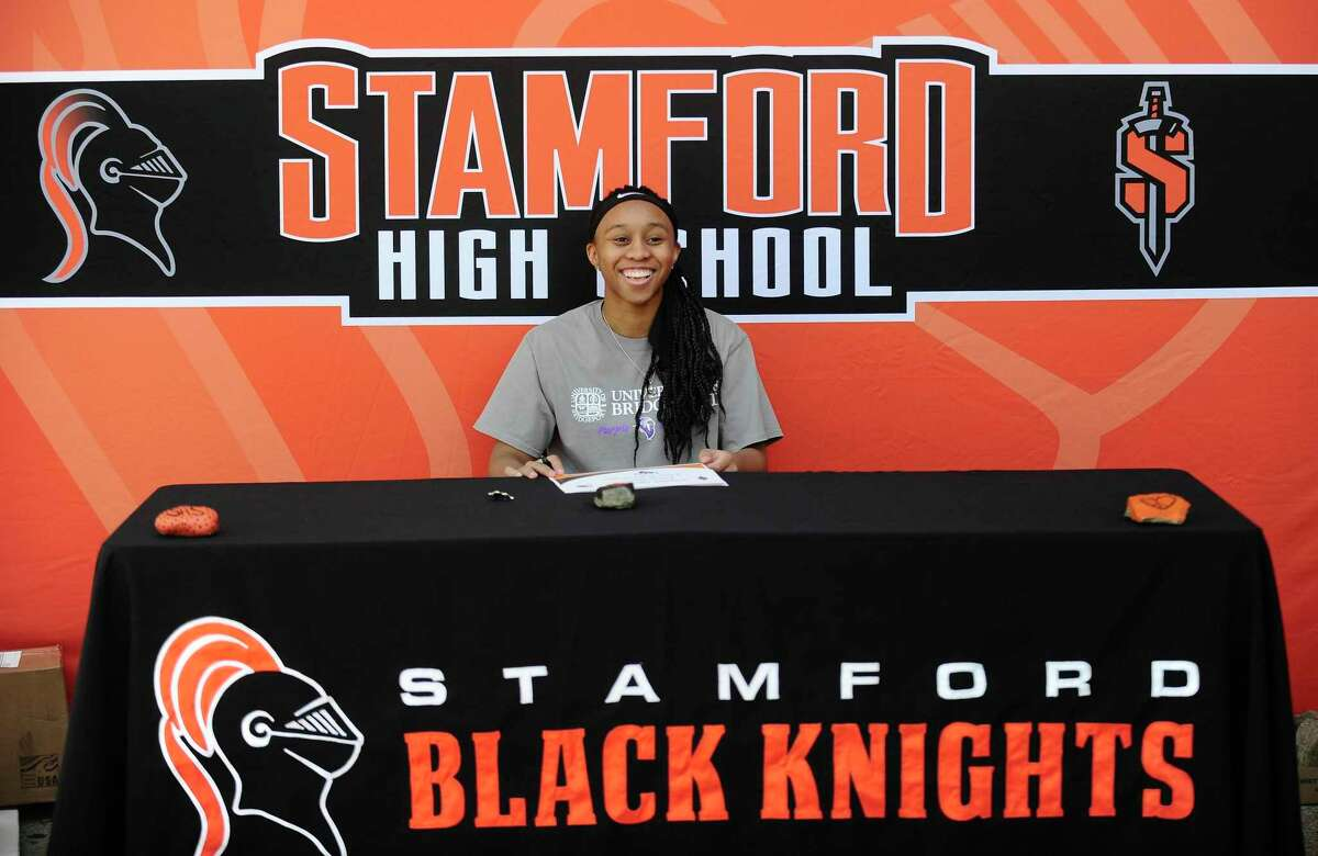 Senior Jessica Nelson signs her commitment to play basketball at the University of Bridgeport on May 20, 2020. Stamford Athletic Director Chris Pasamono put together Socially acceptable way for student athletes and there families to formally sign commitments and have photos taken, keeping with social distancing guidelines in front of the school in Stamford, Connecticut.