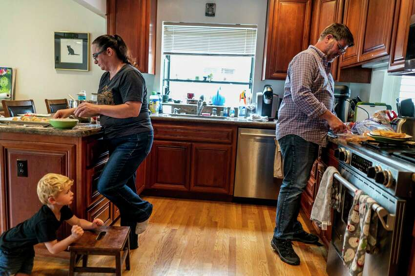 Aimee Rae Hannaford makes cookies with her husband, Tom Baker, while keeping an eye on their 3-year-old son Ryan at their home in Castro Valley, Calif.
