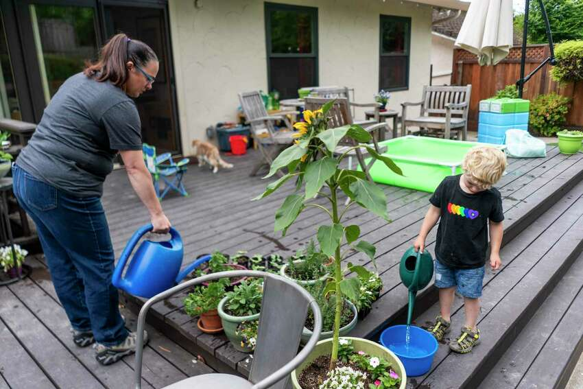 Aimee Rae Hannaford and her son, Ryan, water the plants in the backyard of their home in Castro Valley, Calif.
