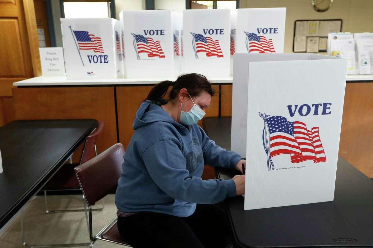 A voter fills out an absentee ballot