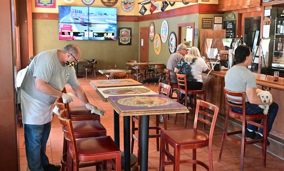 An employee disinfects seating as customers sit at the bar at Downtown Joe's restaurant and bar in Napa, California on May 20, 2020. Taking advantage of Napa's liberalized shelter-in-place rules, some restaurants have begun to fully reopen with new safety requirements in place.