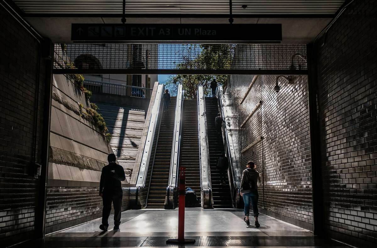 People are seen entering and exiting the Civic Center Bart station in San Francisco on Thursday, May 21, 2020.