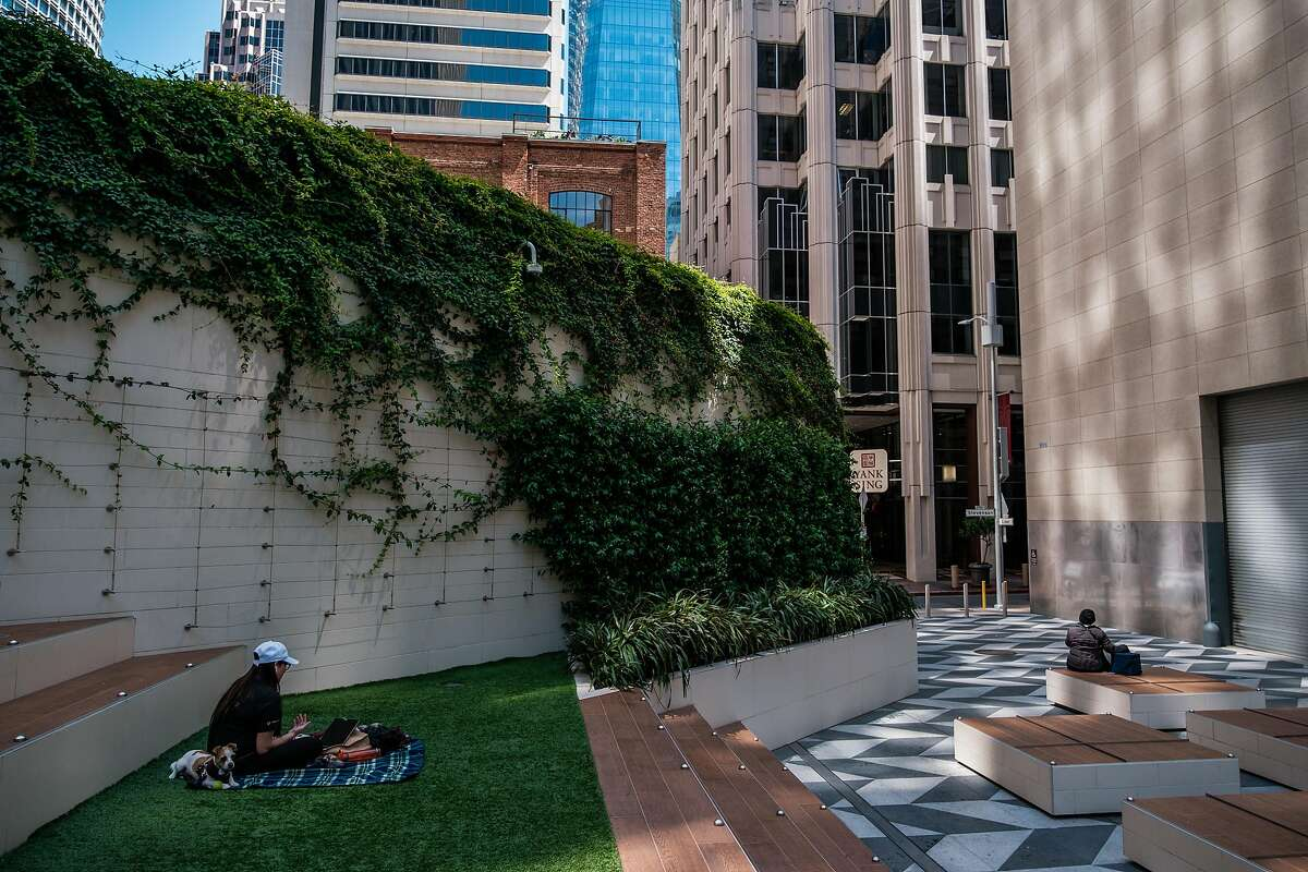 People sit and socially distance in a very quiet downtown San Francisco on Thursday, May 21, 2020.
