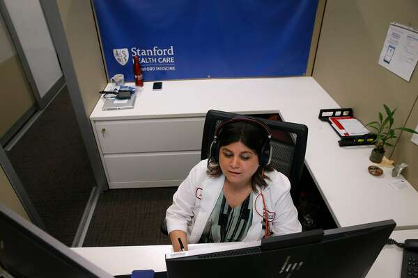 Maria Carla Faccini translates for Spanish-speaking patients from a Stanford Health Care call center who are meeting with their physicians on a remote video appointment in Palo Alto, Calif. on Tuesday, May 12, 2020.
