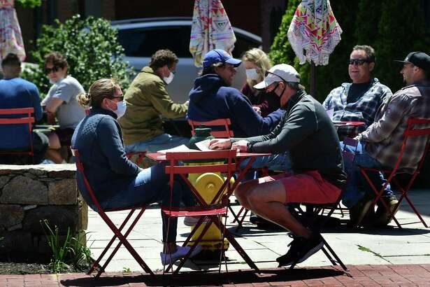 Local residents get out to enjoy the town Wednesday May 20, 2020, including Patrons of Donovan's restaurant during the limited reopening after the quarantine due to the coronavirus outbreak in Norwalk, Conn.