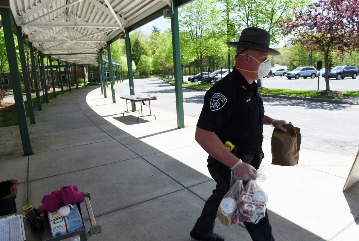 Rensselaer County sheriff's deputy Brian Nikles helps distribute meals at Averill park High School on Friday, May, 22, 2020, in Averill Park, N.Y. Nikels has been a major part of the school's food distribution program since its first day of closure, serving food to all Averill Park students in need. (Will Waldron/Times Union)