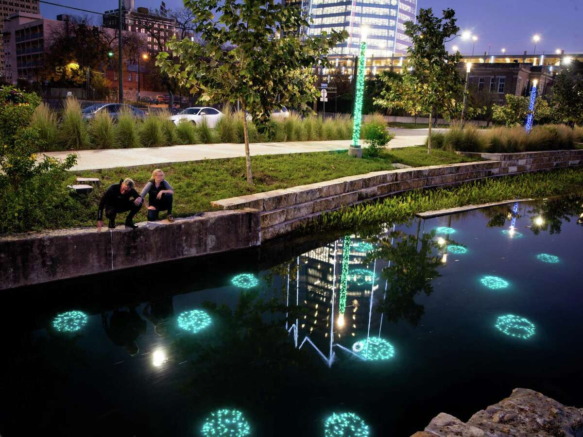 """Artist Ansen Seale, left, and his assistant Crystal Hollis, second left, check on his underwater art piece in San Pedro Creek in San Antonio, Texas on Monday, December 9, 2019. Seale created a public art piece titled, """"Luminous Creek Urchins,"""" for the San Pedro Creek Culture Park as part of the San Antonio River Authority's temporary art program."""
