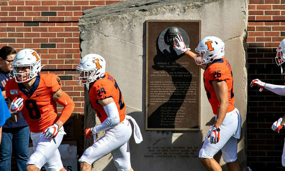 Illini football players touch the Red Grange plaque adjacent to the field at Memorial Stadium for luck prior to a game. The Illinois Division of Intercollegiate Athletics is preparing to return groups of student-athletes to campus for voluntary summer training, with staggered arrivals beginning as early as June 3. Photo: Illinois Athletics