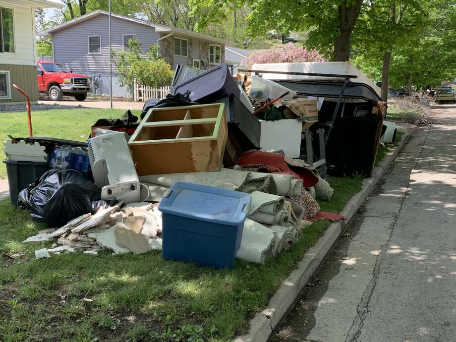 Piles of debris caused by flooded homes sit alongside the curb on Avon Street in Midland, Friday, May 22. Photo: Fred Kelly/fred.kelly@mdn.net