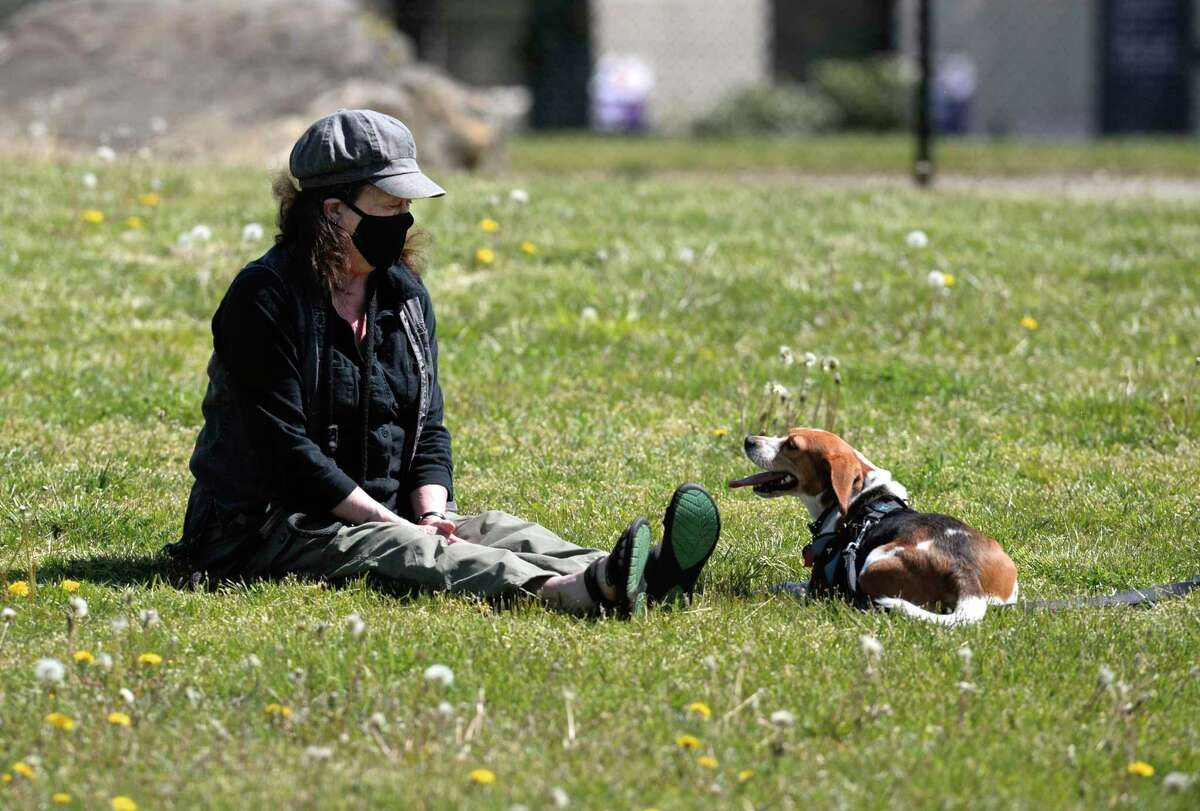 Jean Carlson and Sadie, of Danbury, enjoy the sun at the reopened dog park on Miry Brook Road ,Friday, May 22, 2020, in Danbury, Conn.