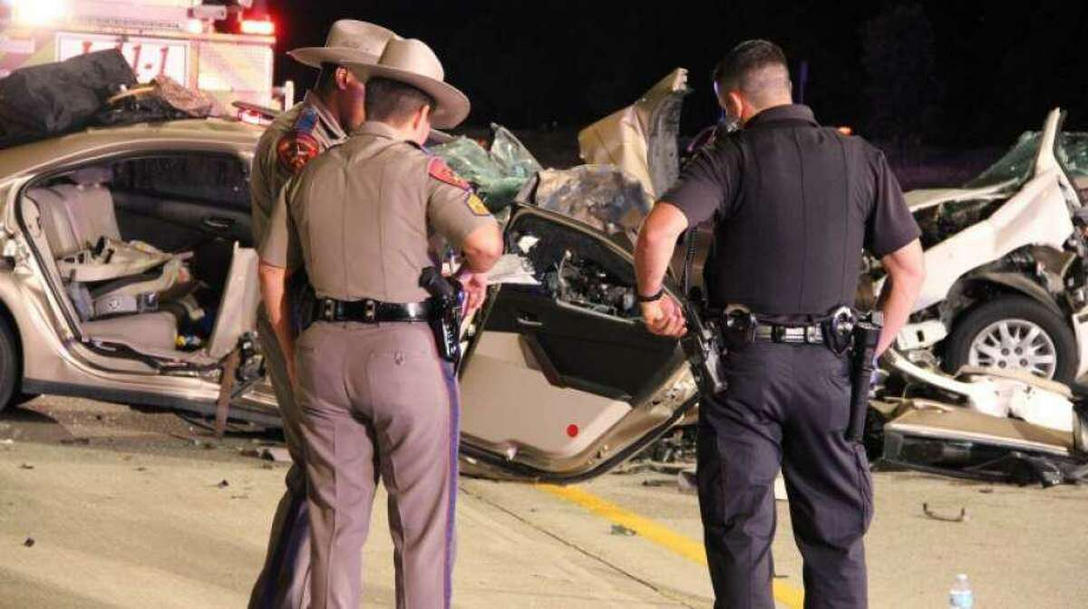 DPS troopers investigate the scene of a crash that killed three people on Interstate 45 North in The Woodlands in July 2012.