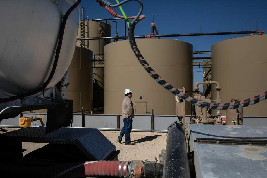 A worker waits as oil is transferred from production tanks to a tanker truck at a Parsley Energy facility near Midland Jan. 24, 2019. As operators shut in wells and facilities to cope with low oil prices, they're urged to take precautions up front to save on repair costs and ensure the equipment is ready once production starts up again. Photo: TAMIR KALIFA/NYT
