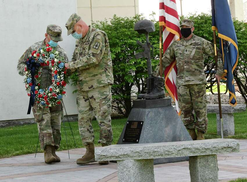 New York State Command Sergeant Major David Piwowarski, left, and Major General Ray Shields carry a wreath to a memorial statue during a traditional Memorial Day ceremony at New York State Division of Military and Naval Affairs Headquarters on Friday, May 22, 2020 in Latham, N.Y. Sergeant Major Roy Sayward is seen holding the United States and New York State flags at right. (Lori Van Buren/Times Union)