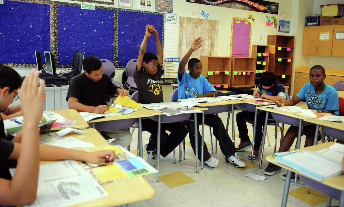 Students in Evelyn Maru's eighth grade summer school class study reading Thursday, July 12, 2012 at Cesar Batalla School in Bridgeport, Conn.