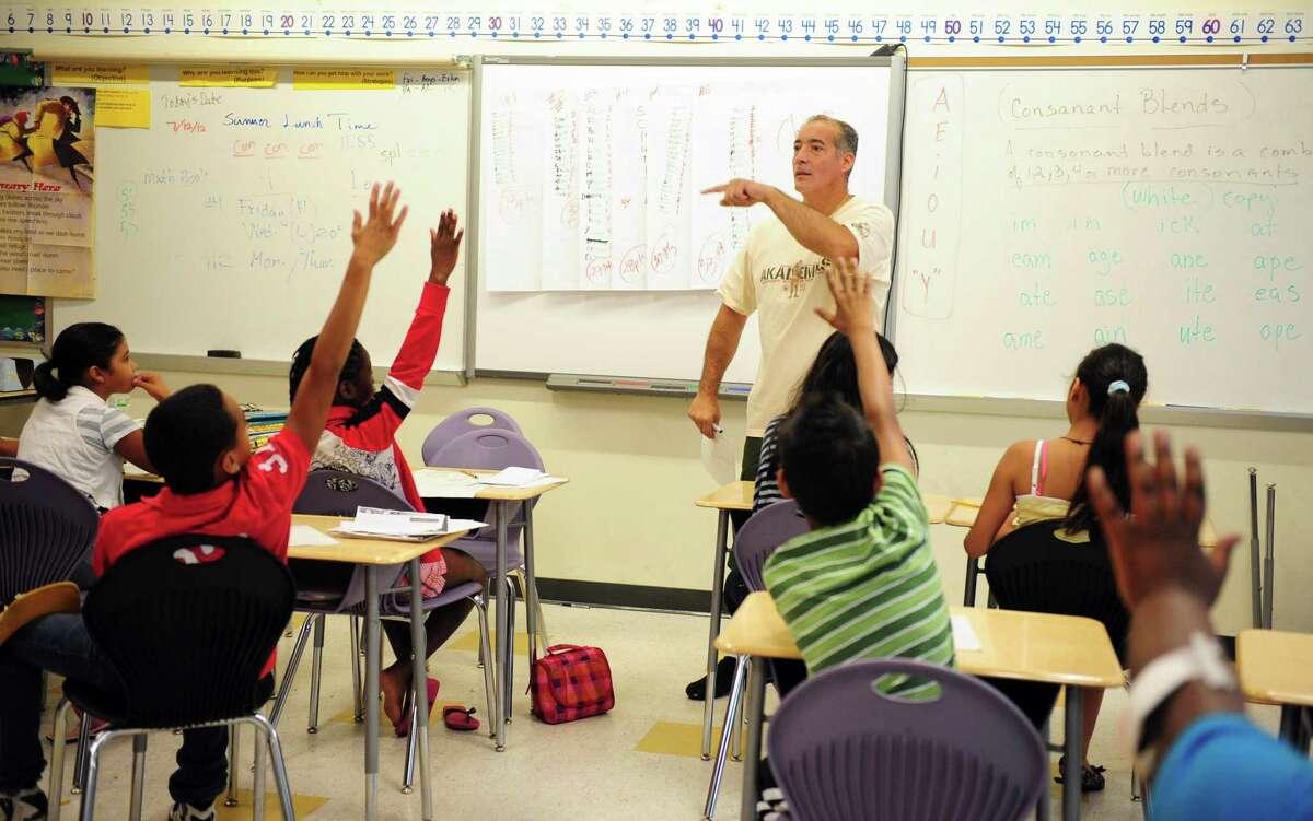 Edwin Quiles teaches math to sixth grade students during summer school Thursday, July 12, 2012 at Cesar Batalla School in Bridgeport, Conn.