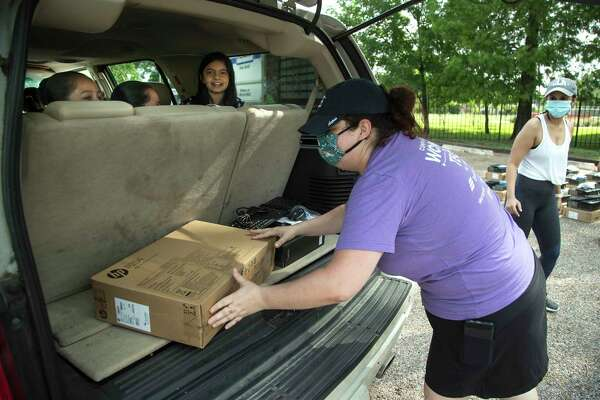 Megan Steckly, CEO of Comp-U-Dot, places a computer in the back of a vehicle Thursday at Houston ISD's Hogg Middle School, where dozens of families lined up to receive free technology from the nonprofit. The novel coronavirus pandemic has prompted Houston ISD officials to aim for providing a district-issued computer to all students in 2020-21, with nonprofits helping to close the digital divide for now.