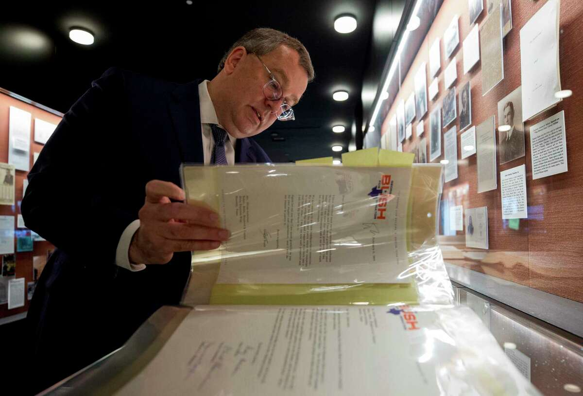 Bill Kroger, Baker Botts L.L.P. head of energy practice, browses through a folder containing correspondence between the law firm and president George H.W. Bush at the downtown office Monday, Dec. 3, 2018, in Houston.