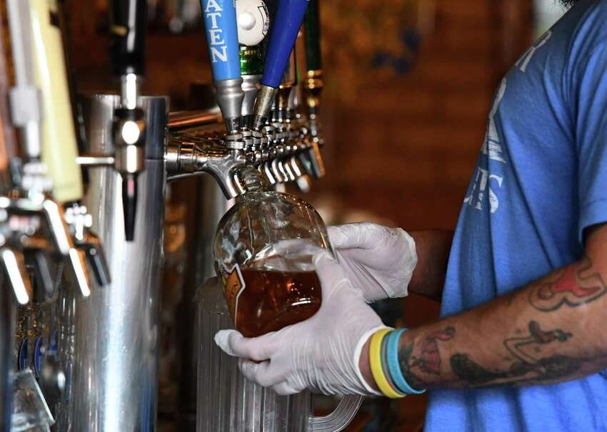 Carl Lewandowski, the manager of Wolff's Biergarten, fills a growler for takeout on Friday, May, 22, 2020, at Wolff's Biergarten in Albany, N.Y. New York's bars and restaurants would continue to be allowed to sell alcohol with takeout/delivery food for two years after the COVID-19 state of disaster emergency ends. (Will Waldron/Times Union)