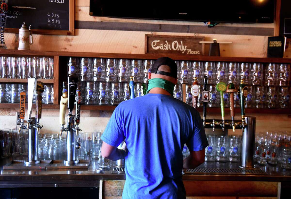 Carl Lewandowski, the manager of Wolff's Biergarten, fills a growler for takeout on Friday, May, 22, 2020, at Wolff's Biergarten in Albany, N.Y. The once cash-only Wolff'swill begin accepting credit cards because of public-health considerations. (Will Waldron/Times Union)