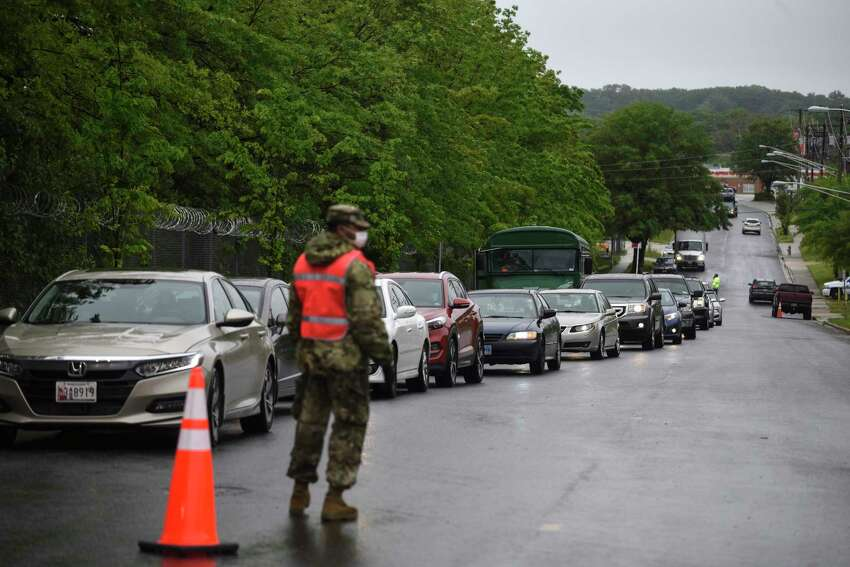 People, in their vehicles line up to get tested for the coronavirus in Hyattsville Friday. The testing, done at a vehicle inspection station, is now open to Maryland residents regardless of whether they show symptoms or have a doctor's referral.