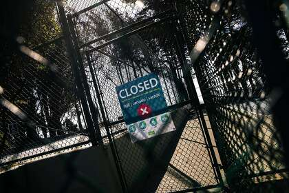 A closed sign can be seen on a locked entrance to the tennis court in Holly Park, which occurred during the coronavirus disease (COVID-19) outbreak on Thursday, May 21, 2020 in San Francisco, California.