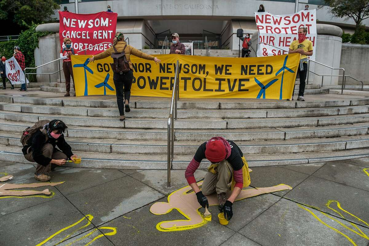 Protesters unfurl banners and paint human chalk outlines depicting lives lost during fires caused by PG&E in San Francisco on Wednesday, May 20, 2020.
