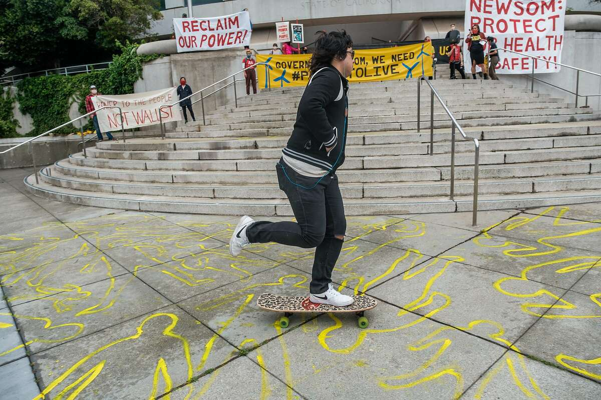 A person skateboards over human chalk outlines depicting lives lost during fires caused by PG&E as he rolls past a protest in San Francisco on Wednesday, May 20, 2020.