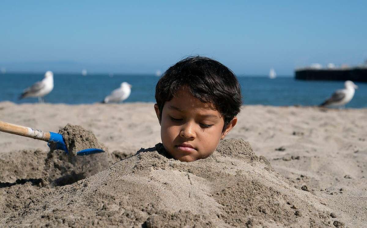 Troy Perry, 8, is buried in the sand on Santa Cruz Beach on Wednesday, April 22, 2020 in Santa Cruz, Calif.
