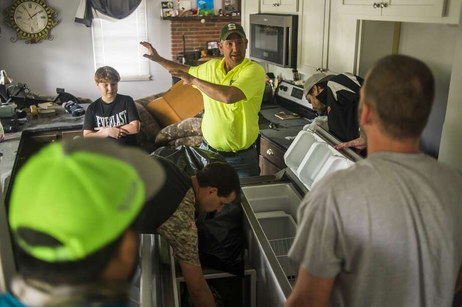 Matt McQuaid, center, and his son Zander, 9, back left, chat with friends who volunteered to help as they work to clear out the refrigerator in the McQuaids' home, which was devastated by flooding, Friday, May 22, 2020 on E. Pine River Road in Midland. (Katy Kildee/kkildee@mdn.net) Photo: (Katy Kildee/kkildee@mdn.net)
