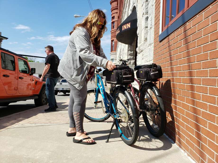 Suzanne Ferris, of Okemos, adjusts her bicycle in downtown Manistee Friday afternoon during a visit during the holiday weekend.  Photo: Arielle Breen/News Advocate