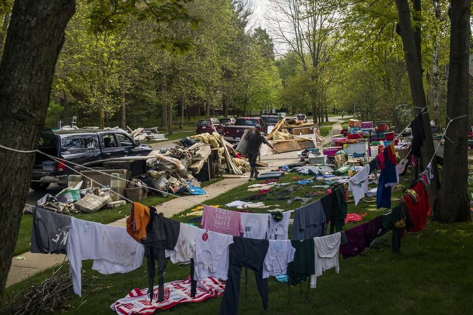 Articles of clothing lie in the sun to dry as the Nicholas family works to clear out the basement of their home on Abigail Lane, which was devastated by flooding, Friday, May 22, 2020 in Midland. (Katy Kildee/kkildee@mdn.net) Photo: (Katy Kildee/kkildee@mdn.net)
