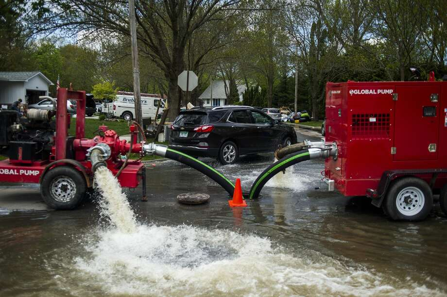 Water pumps are utilized to reduce the amount of water which collected in many basements in the area near Abigail Lane near Drake Street and Saginaw Road Friday, May 22, 2020 in Midland. (Katy Kildee/kkildee@mdn.net) Photo: (Katy Kildee/kkildee@mdn.net)