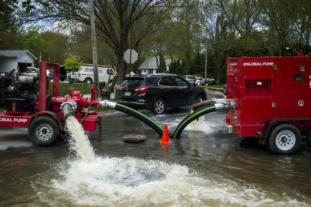 Water pumps are utilized to reduce the amount of water which collected in many basements in the area near Abigail Lane near Drake Street and Saginaw Road Friday, May 22, 2020 in Midland. (Katy Kildee/kkildee@mdn.net)