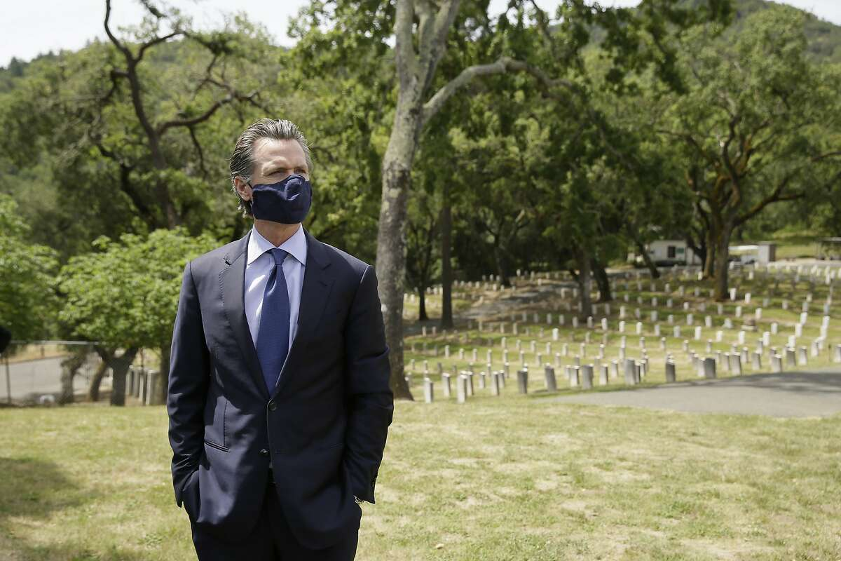 California Gov. Gavin Newsom looks out at rows of graves before a wreath laying ceremony in the cemetery at the Veterans Home of California Friday, May 22, 2020, in Yountville, Calif. (AP Photo/Eric Risberg, Pool)