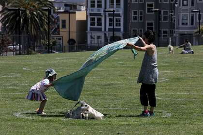 Liore Milgrom-Gartner and her daughter find a spot to place their blanket at Dolores Park in San Francisco.