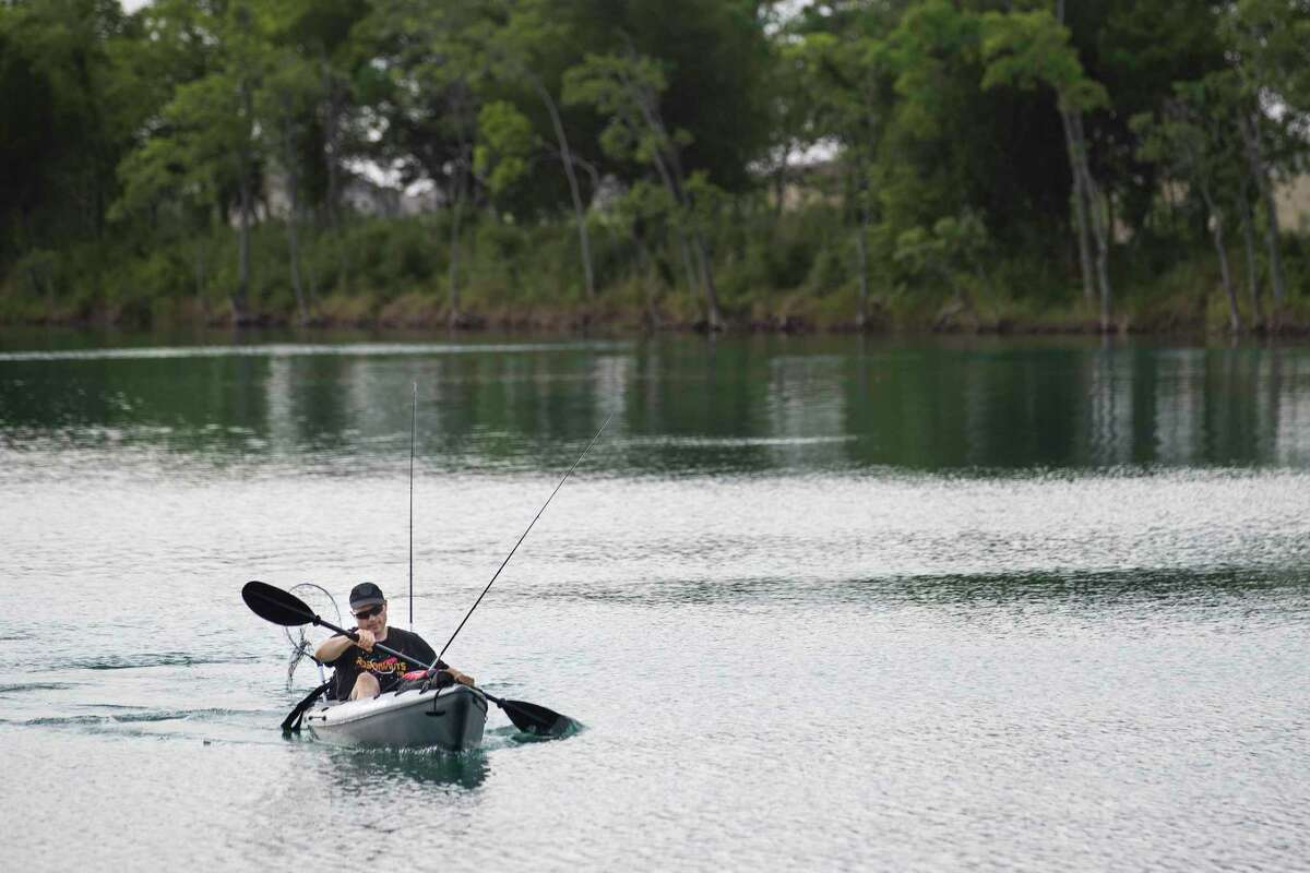 Drew Price paddles in to shore after fishing at Lake Friendswood Park on Friday, May 22, 2020 in Friendswood.