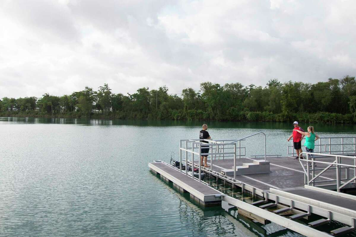 Drew Price, left, talks to Virgil Mikeska and Jana Giovannini on a dock at Lake Friendswood Park on Friday, May 22, 2020 in Friendswood.