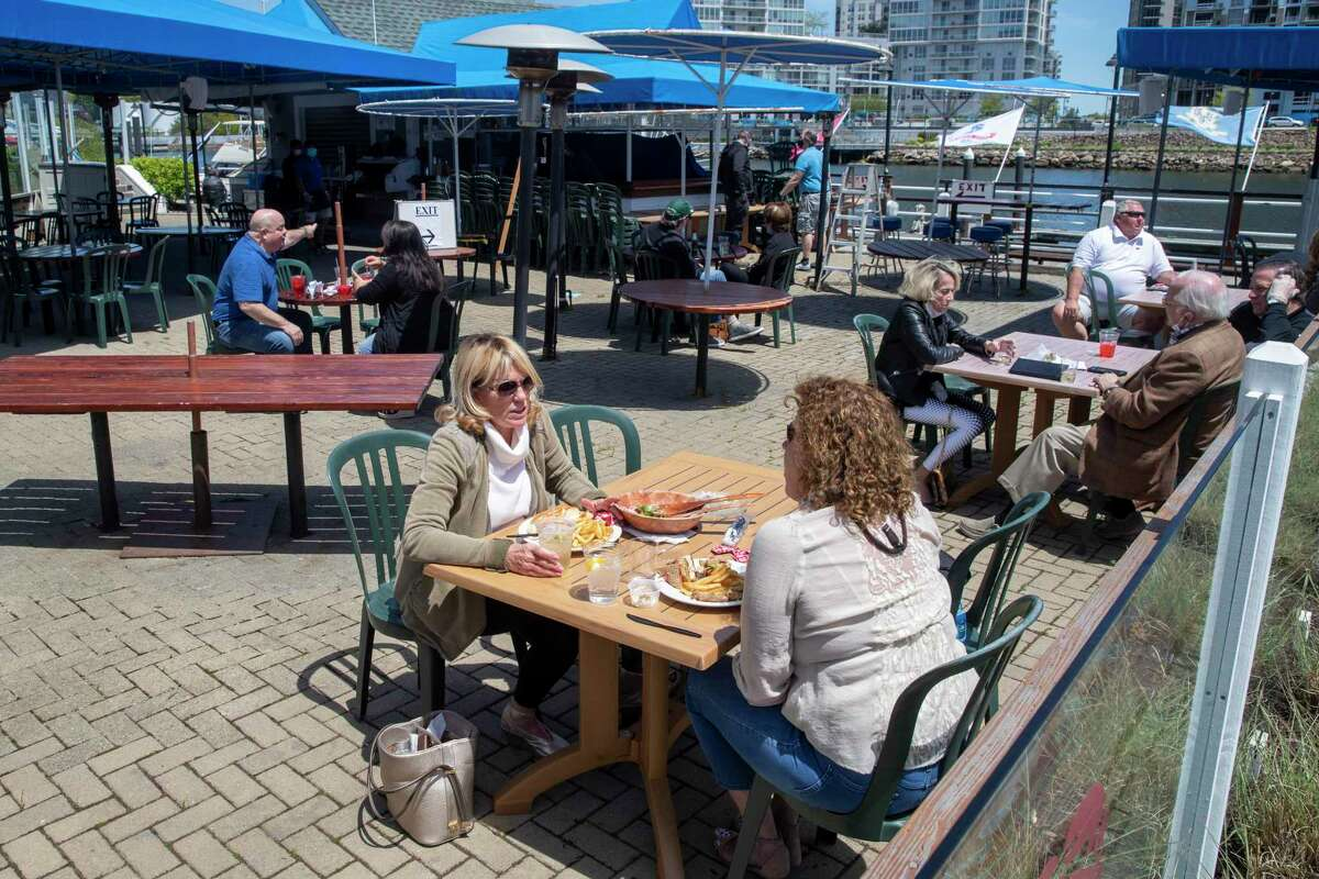 Patrons enjoy lunch on the patio of the Crab Shell restaurant, Wednesday, May 20, 2020, in Stamford, Conn. Restaurants began offering service in outdoor dining areas Wednesday as part of the first phase of Connecticut's statewide reopening, including in hard-hit Fairfield County.