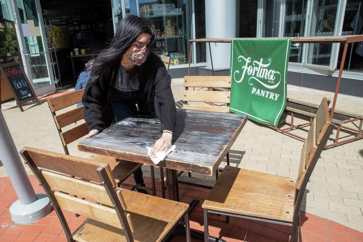 An employee at Fortina restaurant disinfects an outdoor table in preparation for the opening of outdoor dining, Wednesday, May 20, 2020, in Stamford, Conn. Restaurants began offering service in outdoor dining areas Wednesday as part of the first phase of Connecticut's statewide reopening.