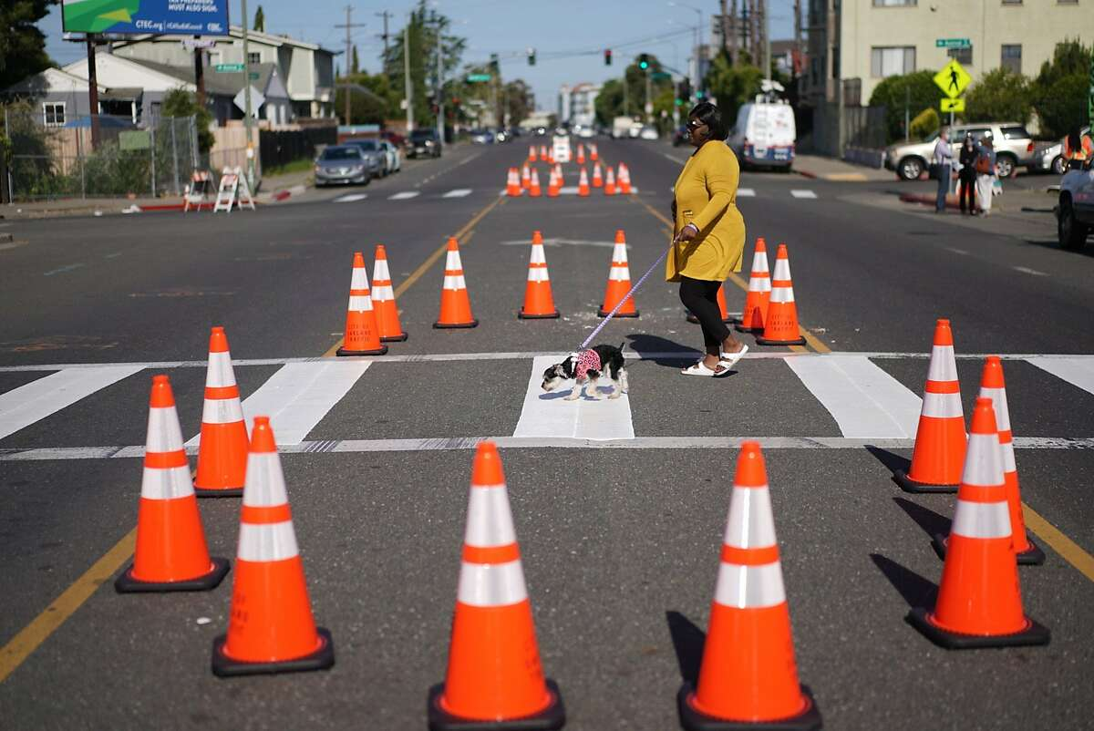 """Veronica Clay with her dog �Jersey� walks among newly placed traffic cones Oakland Mayor Libby Schaaf and the Oakland Department of Transportation had placed on Bancroft Ave. for a pilot program tentatively called """"Slow Streets Essential Places� on Friday, May 22, 2020, in Oakland, Calif."""