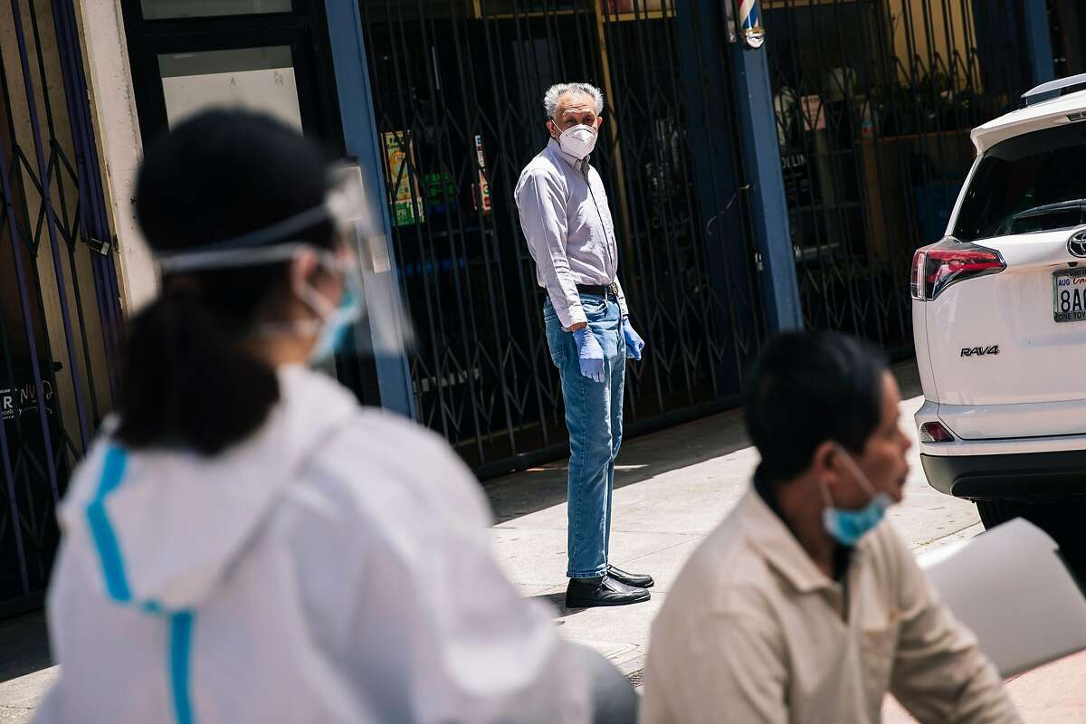 A man watches from a distance as health workers prepare nasal swab tests for the COVID-19 coronavirus disease for residents of the Hoy Sun Ning Yung Benevolent Association on Chinatown's Waverly Place in San Francisco, Calif. on Friday, May 22, 2020.