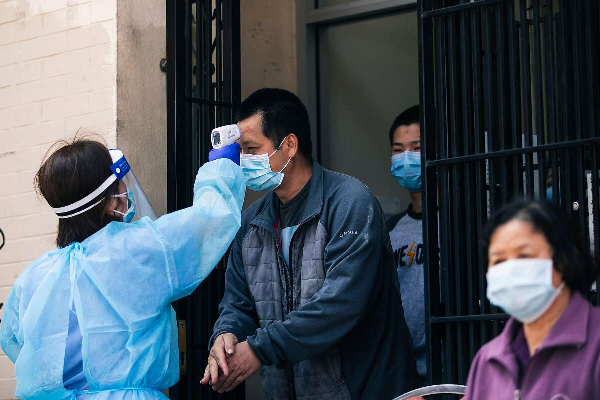 A resident from Hoy Sun Ning Yung Benevolent Association on Chinatown's Waverly Place undergoes a temperature check prior to receiving a test for the COVID-19 coronavirus disease during a joint pilot program with the Chinese Hospital and the San Francisco Department of Public Health in San Francisco, Calif. on Friday, May 22, 2020.