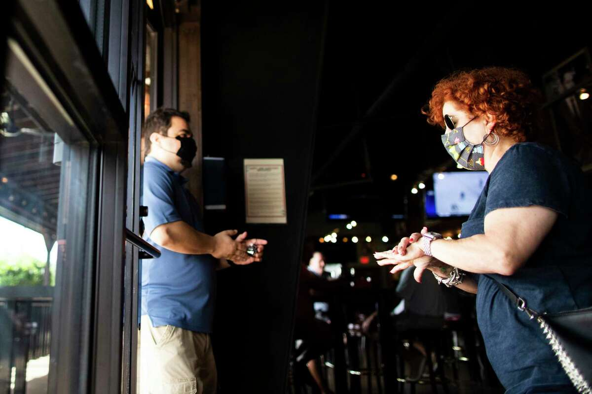 A Kirby Ice House guest rubs her hands after applying hand sanitizer as she exits the bar on Friday, May 22, 2020, in Houston. Friday is the first day that bars have been allowed to open to guests.