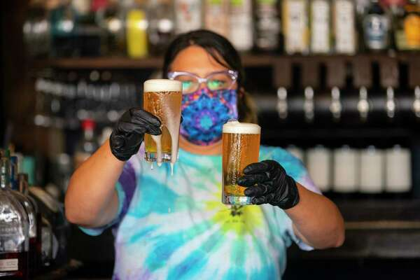 Bartender Melise Rodriguez transfers to freshly poured beers to a serving tray, Friday, May 22, 2020, at Eight Row Flint in Houston. Friday was the first day that bars were allowed to reopen in Texas.