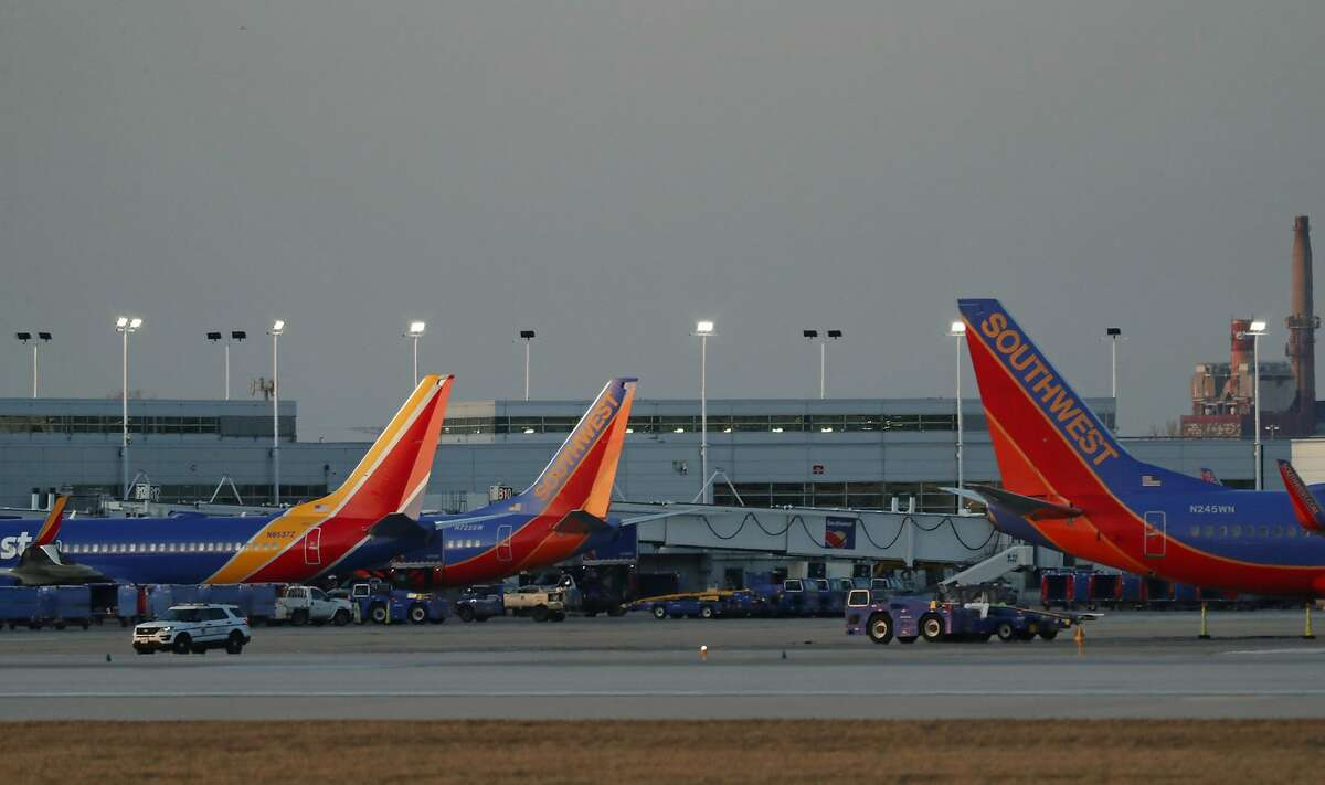 Southwest Airlines planes are parked at gates at Midway International Airport in Chicago on March 17, 2020. Despite deep fare cuts, it doesn't seem likely many Americans will be doing their summer travel by air this year.