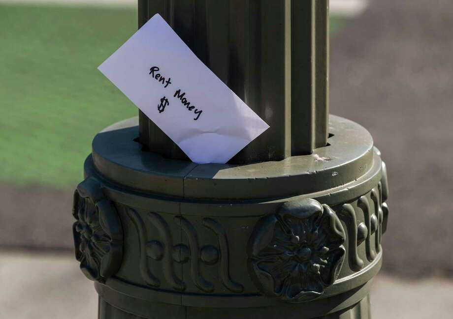 """FILE - In this April 1, 2020, file photo, a paper envelope written with the words """"Rent Money $"""" is left tucked in a lighting pole in the Boyle Heights east district of the city of Los Angeles. When you dona€™t know how to pay the rent next month, first turn to options besides high-interest loans. Outside of cutting nonessential expenses, you can explore government assistance, crowdfunding, industry grants, rental help through nonprofit organizations, and other alternatives to debt. (AP Photo/Damian Dovarganes, File) Photo: Damian Dovarganes / Copyright 2020 The Associated Press. All rights reserved."""